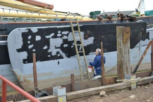 Richard Weekes paints a leeboard in drydock